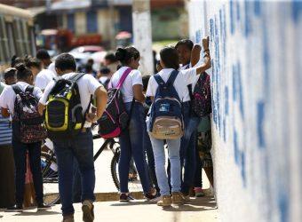 imagem de crianças em um ponto de ônibus com roupa escolar e mochila