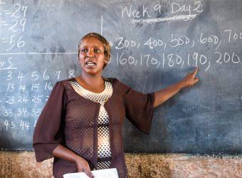 professora dando aula, apontando para lousa